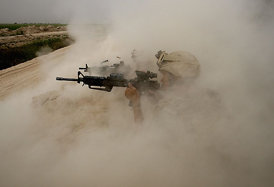 In this May 2, 2008 file photo, U.S. Marines, from the 24th Marine Expeditionary Unit, return fire on Taliban positions near the town of Garmser in Helmand Province of Afghanistan. (AP Photo/David Guttenfelder, File)