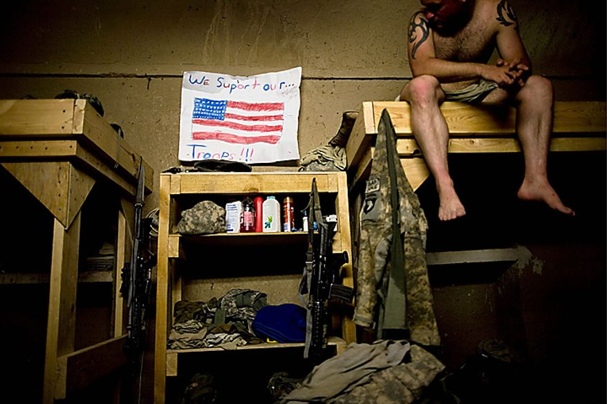 In this Thursday, July 29, 2010 file picture, Spc. Dallas Purdy from Hockley, Texas, hangs a message of support from friends Ashley and Katie Daniels while serving with the 1-320th Alpha Battery, 2nd Brigade of the 101st Airborne Division at COP Nolen, in the volatile Arghandab Valley, Kandahar, Afghanistan. (AP Photo/Rodrigo Abd, File)