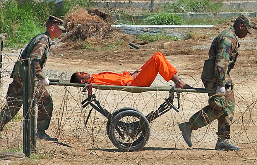 In this Feb. 2, 2002 file photo, a suspected al-Qaida or Taliban detainee from Afghanistan is carried on a stretcher before being interrogated by military officials at the detention facility Camp X-Ray on Guantanamo Bay U.S. Naval Base in Cuba. (AP Photo/Lynne Sladky, File)