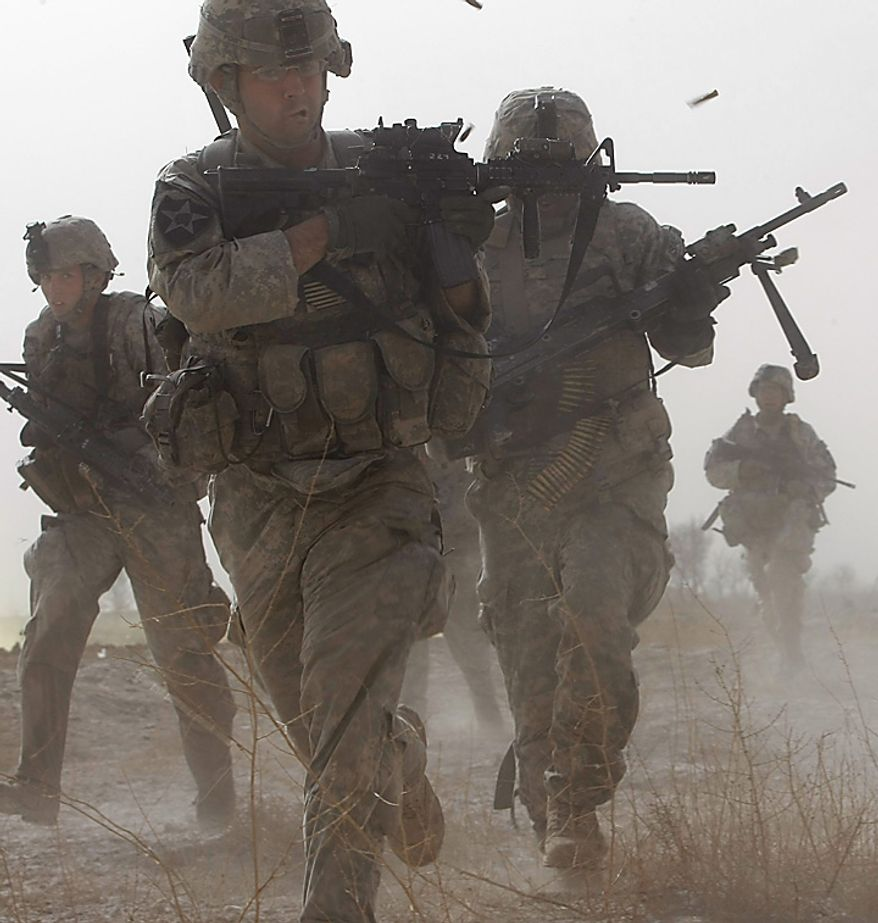 In this Sunday, Feb. 14, 2010 file picture, a U.S. soldier returns fire as others run for cover during a firefight with insurgents in the Badula Qulp area, West of Lashkar Gah  in Helmand province, southern Afghanistan, near Marjah, where U.S. Marines are conducting an offensive against the Taliban. (AP Photo/Pier Paolo Cito, File)