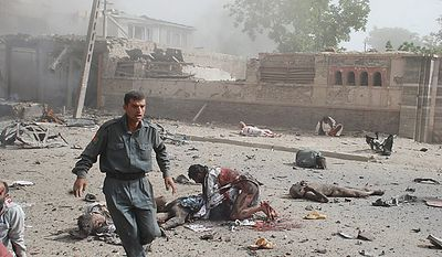 In this July 7, 2008 file photo, an police officer walks among the dead and wounded bodies at the site of a suicide attack near the Indian Embassy in central Kabul, Afghanistan. (AP Photo/Pajhwok News Agency, File)