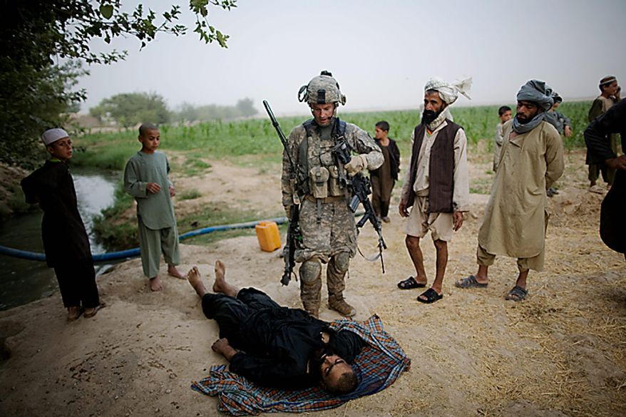 In this Wednesday, July 28, 2010 file picture, U.S. Army Lt. Christopher Babcock looks at the body of a suspected Taliban fighter killed by U.S. soldiers from 1-320th Alpha Battery, 2nd Brigade of the 101st Airborne Division, while local people say the man was a farmer from Samir Kalacha village in the volatile Arghandab Valley, Kandahar, Afghanistan. (AP Photo/Rodrigo Abd, File)