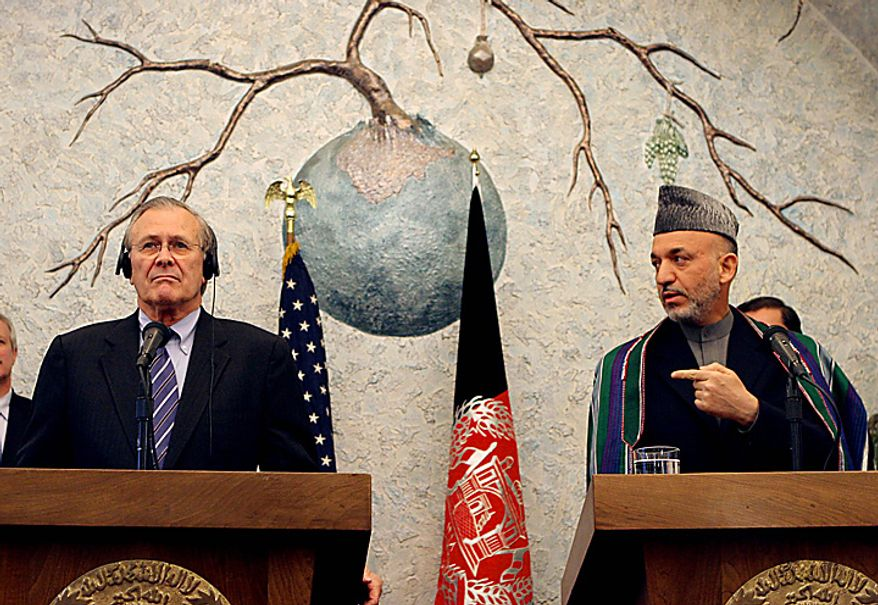** FILE ** In this Wednesday, April 13, 2005, file picture, then-U.S. Secretary of Defense Donald Rumsfeld, left, and Afghan President Hamid Karzai give a news conference in Kabul, Afghanistan. (AP Photo/Tomas Munita, File)