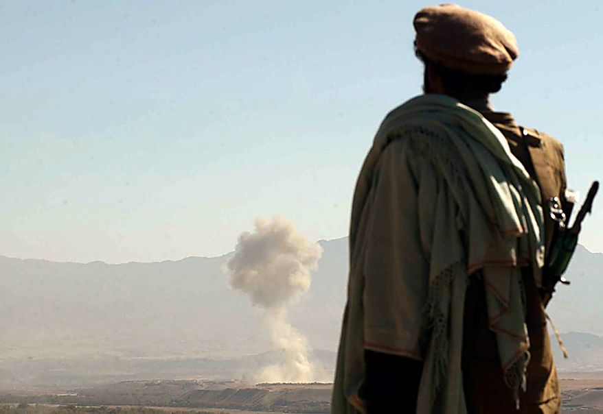 In this Wednesday, Nov. 7, 2001 file picture, an Afghan northern alliance Mujahed looks at a plume of smoke rising from the Taliban village of Khanaqa in the Parwan province, from his position at the Mahmood Raqy frontline in the Kapisa province, 55 kilometers (30 miles) from the Afghan capital Kabul, after an aircraft released it's load of bombs as part of the U.S. attempt to help the northern alliance to advance toward the capital and other key areas. (AP Photo/Marco Di Lauro, File)