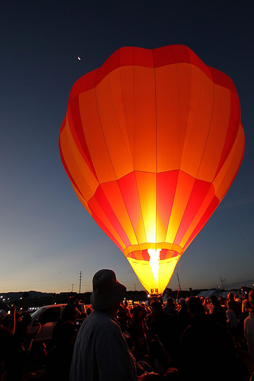 A hot air balloon inflates before the mass ascension at the Albuquerque International Balloon Fiesta in Albuquerque, N.M., on Saturday, Oct. 2, 2010. About 500 balloons were registered for the annual event. (AP Photo/Susan Montoya Bryan)