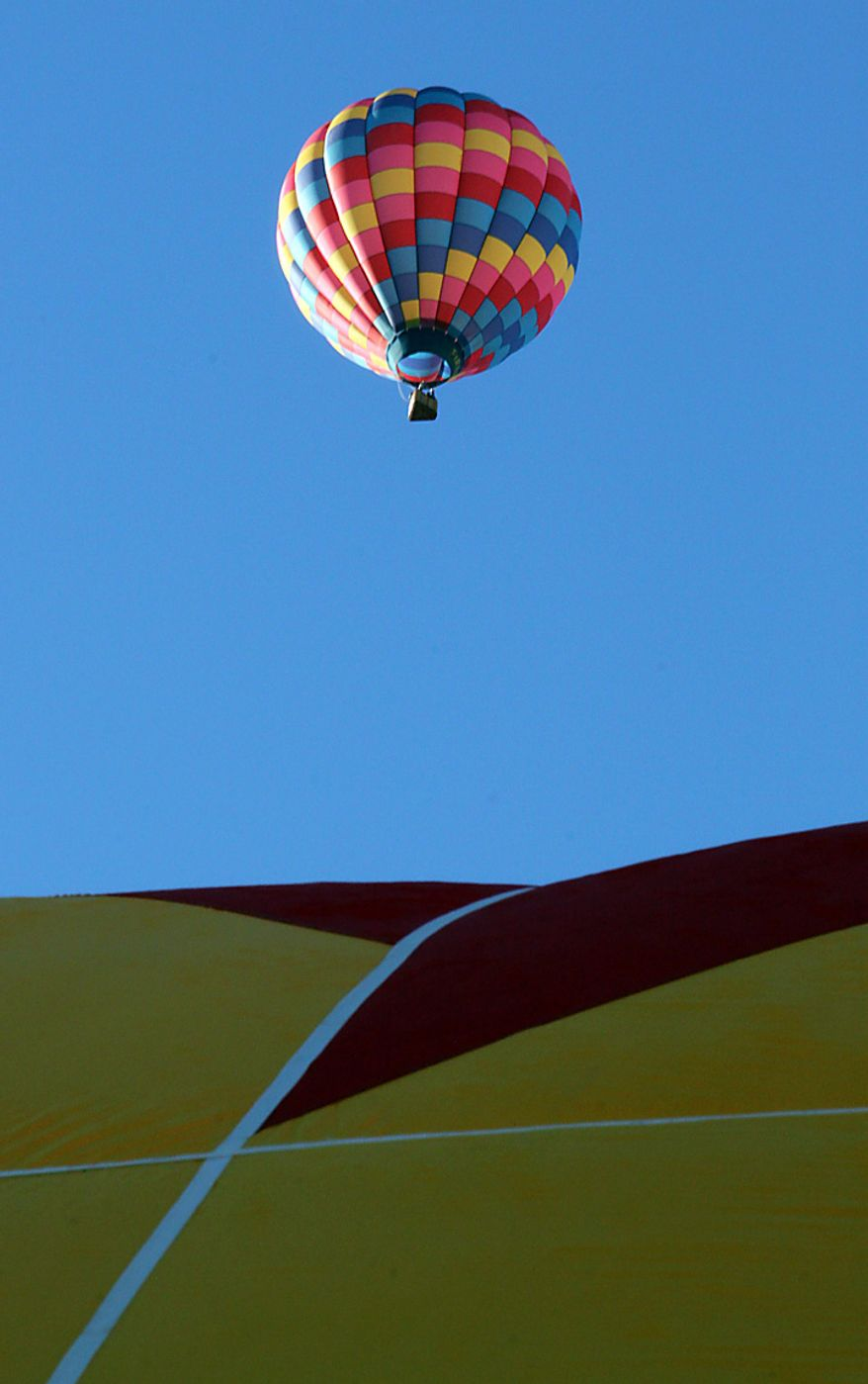 A hot air balloon lifts off during the Albuquerque International Balloon Fiesta in Albuquerque, N.M., on Tuesday, Oct. 5, 2010. The annual event has attracted about 500 balloons and thousands of spectators. (AP Photo/Susan Montoya Bryan)