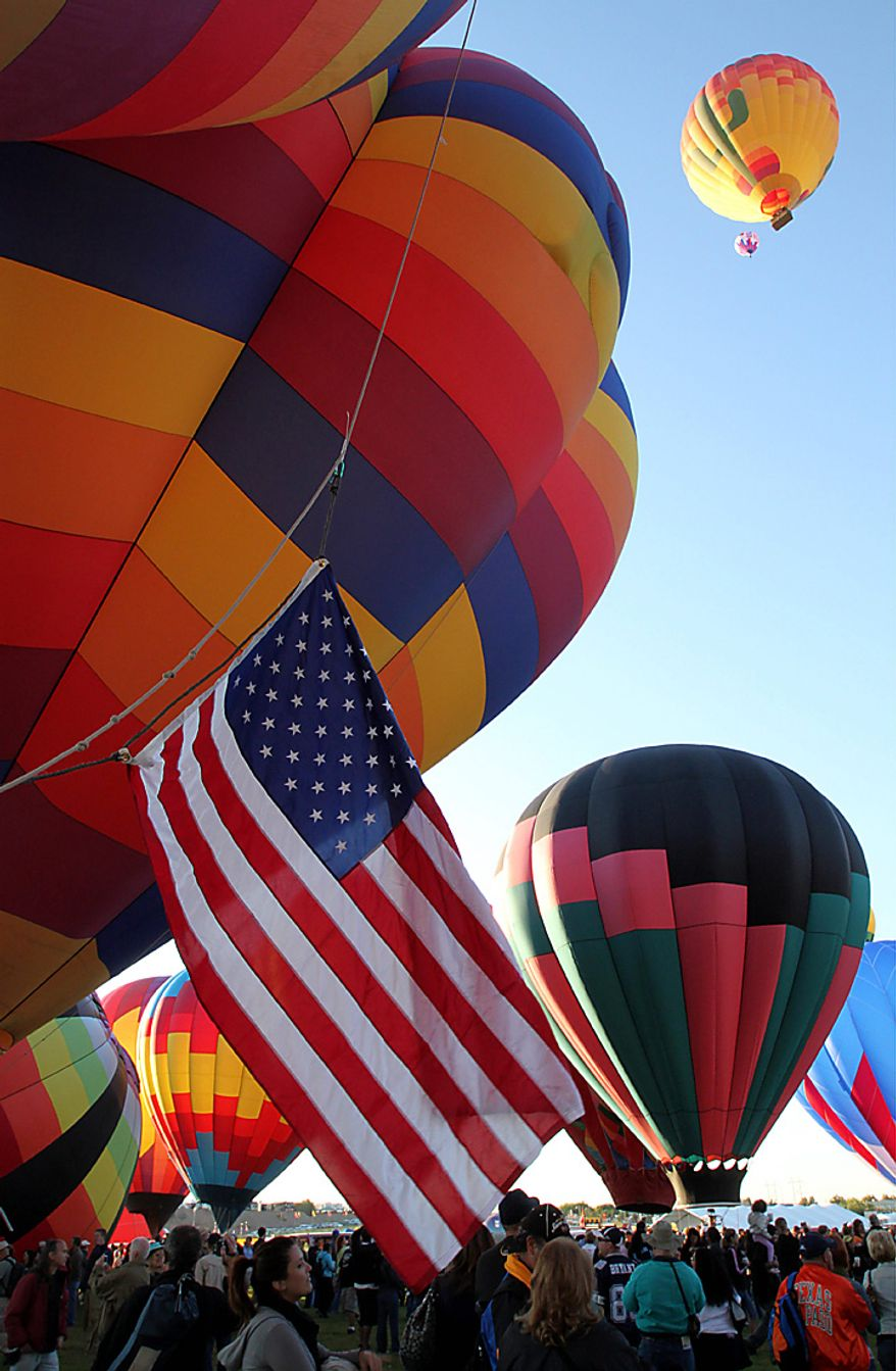 Hot air balloons inflate during the Albuquerque International Balloon Fiesta in Albuquerque, N.M., on Saturday, Oct. 2, 2010. Many balloonists participating in the event are hopeful that missing American pilots Richard Abruzzo and Carol Rymer Davis will be found. The pair went missing over the Adriatic Sea on Wednesday during a European gas balloon race. (AP Photo/Susan Montoya Bryan)