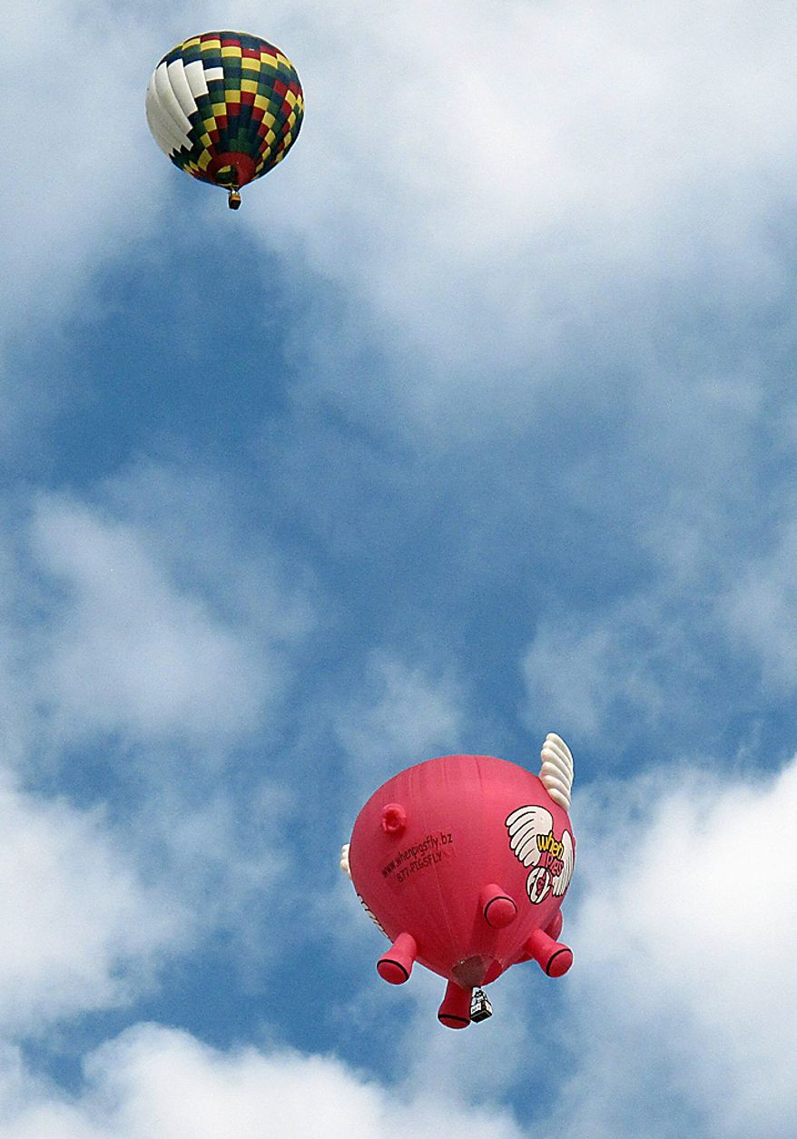 Hot air balloons, including a flying pig, float over Albuquerque, N.M., on the third day of the Albuquerque International Balloon Fiesta Monday, Oct. 4, 2010. (AP Photo/Tim Korte)