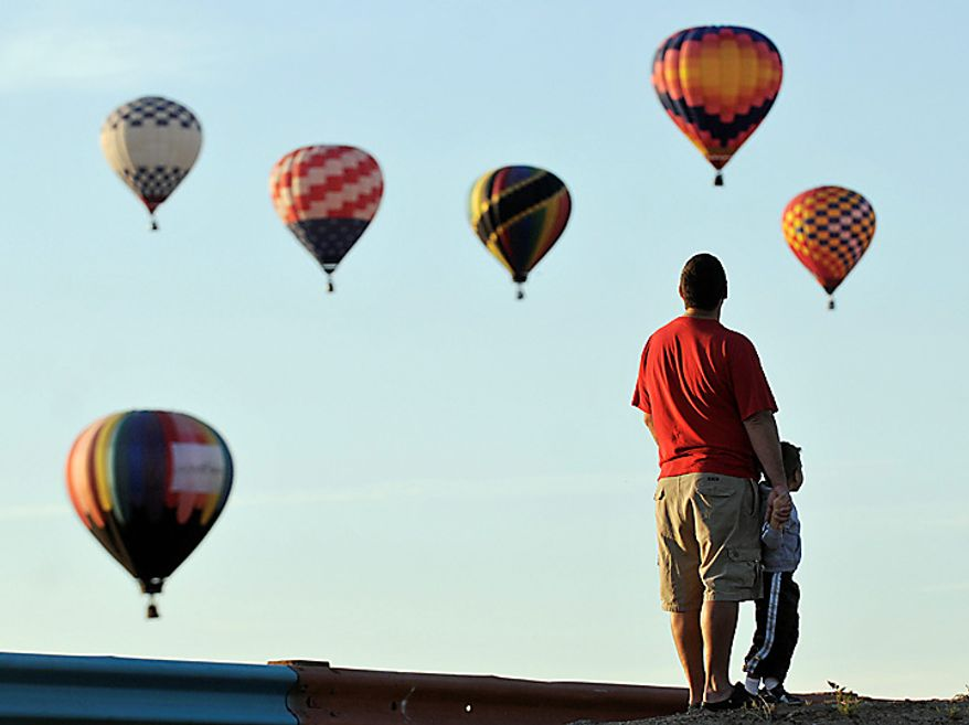 """Matt Brenner and his son Grey, 3, of Rio Rancho, watch mass ascension just north of Balloon Fiesta Park, on the first morning of the Albuquerque International Balloon Fiesta, Saturday, Oct. 2, 2010, in Albuquerque, N.M. """"There's lots of balloons,"""" Grey said. (AP Photo/Albuquerque Journal, Marla Brose)"""