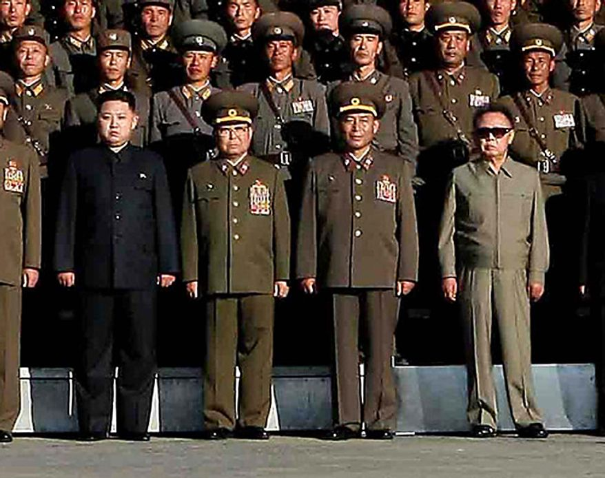 In this undated photo released on Wednesday, Oct. 6, 2010 by Korean Central News Agency via Korea News Service, North Korean leader Kim Jong Il, front right, and his third son Kim Jong Un, front left, pose with North Korean soldiers who participated in a coordinated drill of a military unit of the Korean People's Army at an undisclosed location in North Korea.  North Korea's heir apparent observed military drills with his father, according to a state media report Tuesday, heralding a growing public profile for Kim Jong Un as he takes on a more prominent role in the reclusive nation. Chief of the General Staff of the Korean People's Army Ri Yong Ho stands at second right in front and Defense Chief Kim Yong Chun stands at second left in front. (AP Photo/Korean Central News Agency via Korea News Service)