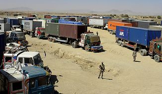 Pakistani border guards stand on alert at a terminal of Afghanistan-bound NATO trucks parked at the Pakistani border post of Chaman along the Afghanistan border on Wednesday, Oct. 6, 2010. Pakistan blocked a vital supply route in the country's north for U.S. and NATO troops in Afghanistan in apparent retaliation for an alleged cross-border helicopter strike by the coalition that killed three Pakistani frontier troops. (AP Photo/Shah Khalid)