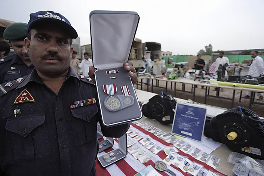 A Pakistani officers shows a medal which is displayed along with other recovered equipment of NATO forces fighting in neighboring Afghanistan, in Peshawar, Pakistan on Monday, Sept. 27, 2010. The paramilitary Frontier Corps has recovered bulk of military gadgets, communication tools and uniforms etc. stolen from NATO convoys in recent months in Pakistan's Khyber tribal region, official said.(AP Photo/Mohammad Sajjad)
