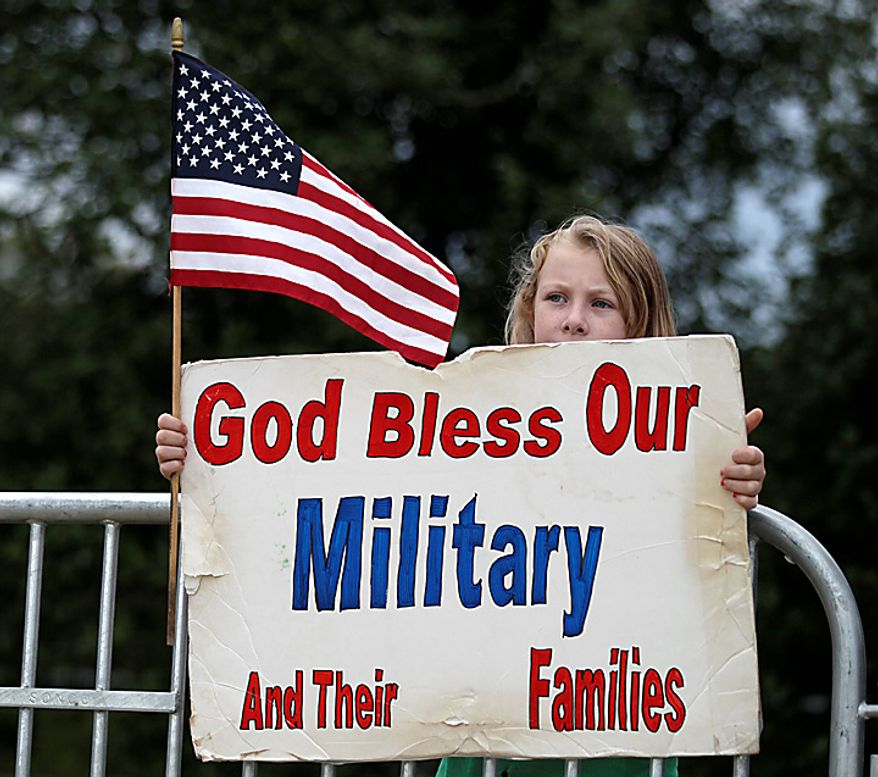 Audrey Low, 10, of Reston, Va., holds a sing as she watches from across the street as members of the Westboro Baptist Church dance on American Flags at Arlington National Cemetery in Arlington, Va., Tuesday, Oct. 5, 2010. (AP Photo/Carolyn Kaster)