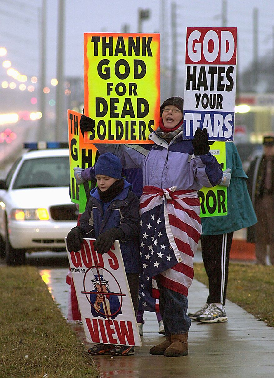 In this Feb. 8, 2006 file photo, Margie Phelps, right, and her nephew, Gabriel Phelps-Roper, then 10, center, both from the Westboro Baptist Church in Topeka, Kan., protest before the start of a memorial service for soldiers killed in combat from the Army's 101st Airborne Division in front of the main entrance to Fort Campbell, Ky. Phelps is set to go before the U.S. Supreme Court on Wednesday, Oct. 5, 2010, to represent her church in a case that tests the scope of free speech protections under the Constitution's First Amendment. (AP Photo/Christopher Berkey, File)