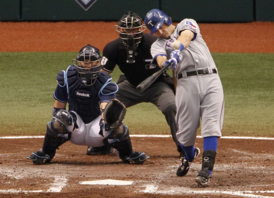 ASSOCIATED PRESS Texas Rangers' Ian Kinsler, right, hits a home run in front of Tampa Bay Rays catcher Kelly Shoppach and home plate umpire Jim Wolf during the fourth inning of Game 2 of baseball's American League Division Series, Thursday, Oct. 7, 2010, in St. Petersburg, Fla.
