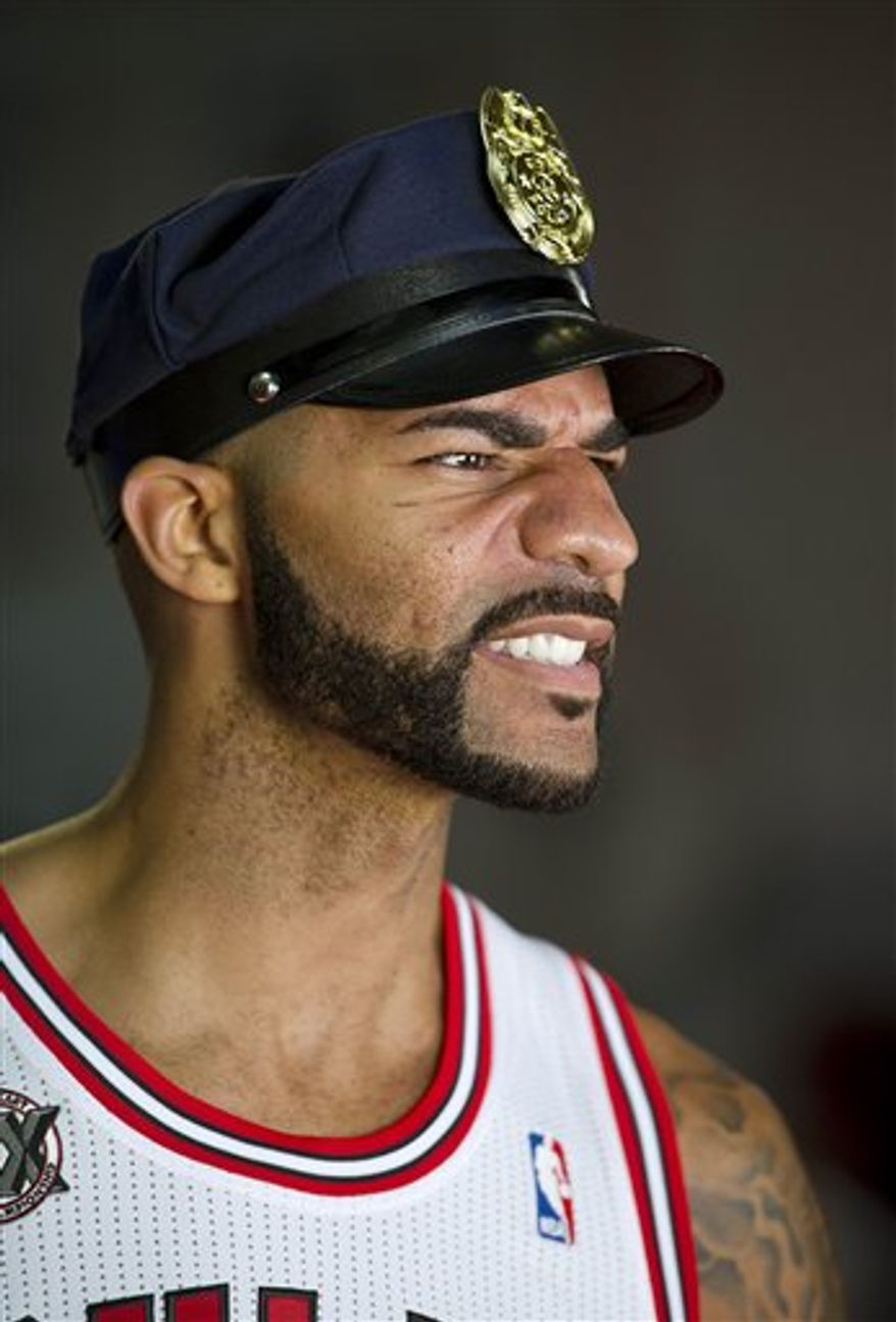 FILE- In this file photo taken Sept. 27, 2010 in Deerfield, Ill., Chicago Bulls' Carlos Boozer snarls for a camera during the NBA basketball team's media day. In the Same day the Chicago Bulls locked in Joakim Noah to a five-year contact, they lost Carlos Boozer for about two months with a broken hand forcing them to have to wait to see how a front court they believe could be one of the best in the NBA will perform. (AP Photo/Jim Prisching)