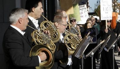 Detroit Symphony Orchestra member Karl Pituch plays his French horn as he serenades fellow members walking a picket line outside the Max M. Fisher Music Center in Detroit, Monday, Oct. 4, 2010. Musicians have called a strike after refusing to accept pay cuts of more than 30 percent demanded by the financially struggling Detroit Symphony Orchestra. (AP Photo/Paul Sancya)