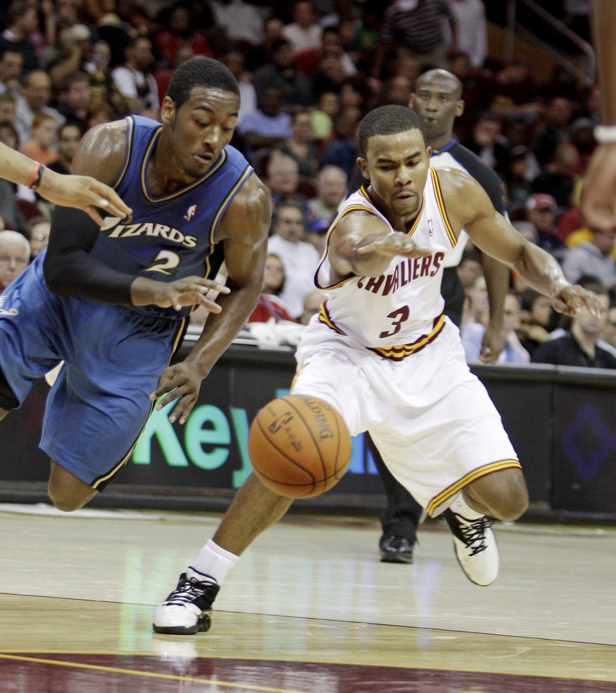 ASSOCIATED PRESS Washington Wizards point guard John Wall (2) and Cleveland Cavaliers point guard Ramon Sessions race for a loose ball in the second quarter of an NBA preseason basketball game Thursday, Oct. 7, 2010, in Cleveland.