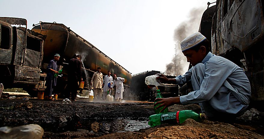 Pakistani villagers collect oil leaked from NATO trucks in Khairabad near Peshawar, Pakistan on Thursday, Oct. 7, 2010. Gunmen in northwest Pakistan torched a dozen tankers carrying fuel to NATO troops police said, the latest strike against supply convoys heading for Afghanistan since Pakistan shut a key border crossing last week. (AP Photo/B.K.Bangash)