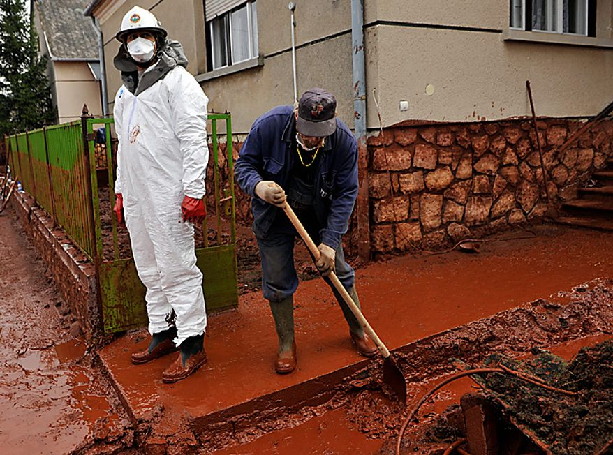 A villagers cleans his yard flooded by toxic mud in Kolontar, Hungary, Thursday, Oct. 7, 2010. The toxic red sludge that inundated three Hungarian villages reached Europe's mighty Danube River on Thursday but no immediate damage was evident, Hungary's rescue operations agency said. The European Union and environmental officials had feared an environmental catastrophe affecting half a dozen nations if the red sludge, a waste product of making aluminum, contaminated Europe's second-longest river after bursting out of a factory's reservoir. (AP Photo/Bela Szandelszky)