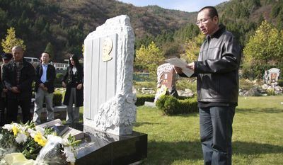 This Oct. 28, 2008, file photo shows Liu Xiaobo, right, reading a letter beside the grave of Bao Zunxin, a Chinese historian and political dissident who was arrested and jailed for his role in the 1989 Tiananmen Square democracy protests in Beijing, China. Mr. Liu won the 2010 Nobel Peace Prize on Friday Oct. 8, 2010. (AP Photo, File)