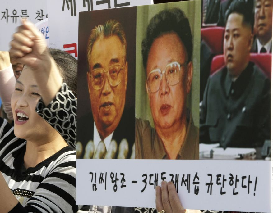 "A North Korean defector shouts slogans next to a placard showing photos of North Korean leader Kim Jong-il, center, his late father Kim Il-sung, left, and his youngest son Kim Jong-un, during a rally against the North's succession in Seoul, South Korea, Friday, Oct. 8, 2010. The letters on a banner read ""We denounce the family's succession through three generations."" (AP Photo/Ahn Young-joon)"