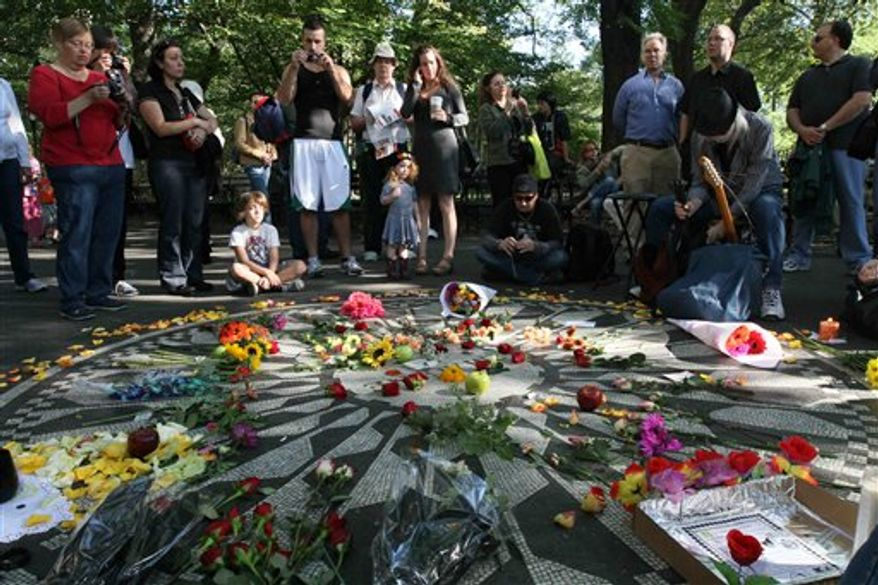 People gather around the Imagine mosaic in Strawberry Fields in New York's Central Park, Saturday, Oct. 9, 2010. This would have been John Lennon's 70th birthday. (AP Photo/Tina Fineberg)
