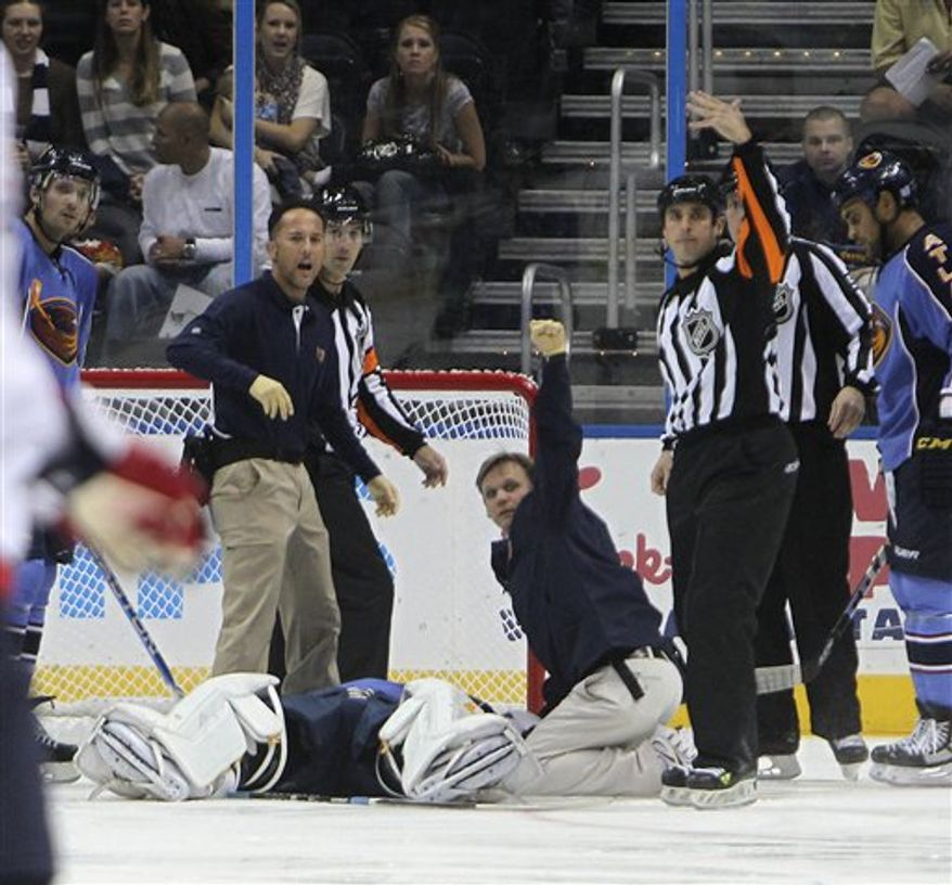 Atlanta Thrashers medical personal signal for a stretcher as they work on Atlanta Thrashers goalie Ondrej Pavelec after he collapsed in the first period of an NHL hockey game against the Washington Capitals  Friday, Oct. 8, 2010 in Atlanta., (AP Photo/John Bazemore)