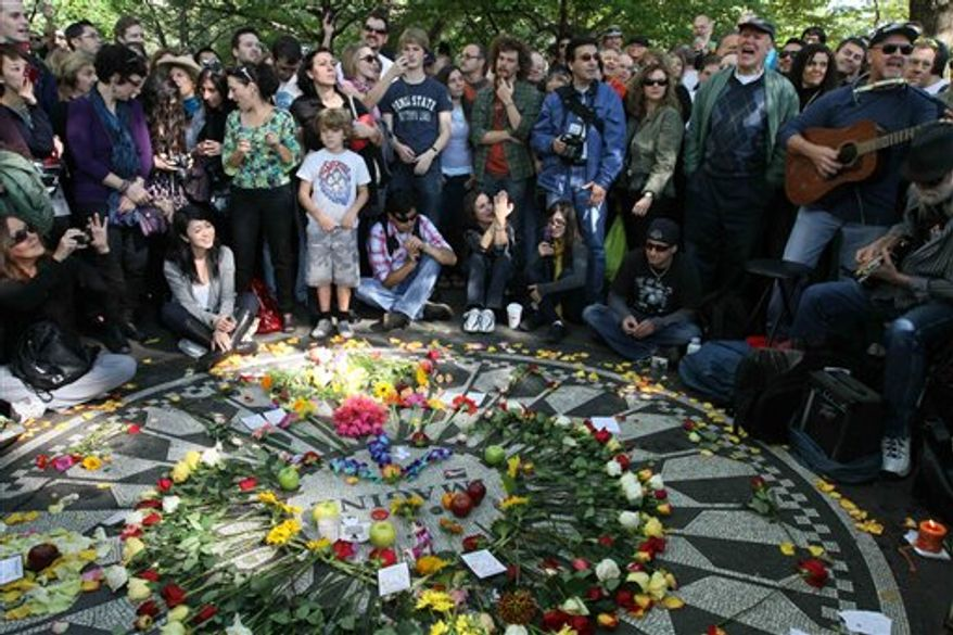 Julia Balk, seated right, spreads flower petals on the Imagine mosaic as she spends time in Strawberry Fields in New York's Central Park on Saturday, Oct. 9, 2010, the day that would have been John Lennon's 70th birthday. (AP Photo/Tina Fineberg)