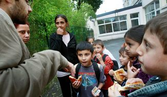French teacher Justin Lyot (left) talks to Roma children, including Abel Bot, 8, (center) as they leave school in Choisy-le-Roi, France. Education woes include segregated schools in Eastern Europe and the systematic misdiagnosis of mental disabilities. (Associated Press)
