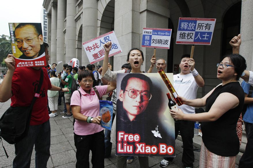 """Pro-democracy protesters hold a picture of Chinese dissident Liu Xiaobo and signs reading """"Release Liu Xiaobo"""" as they march to the China's liaison office in Hong Kong on Sunday, Oct. 10, 2010. (AP Photo/Kin Cheung)"""