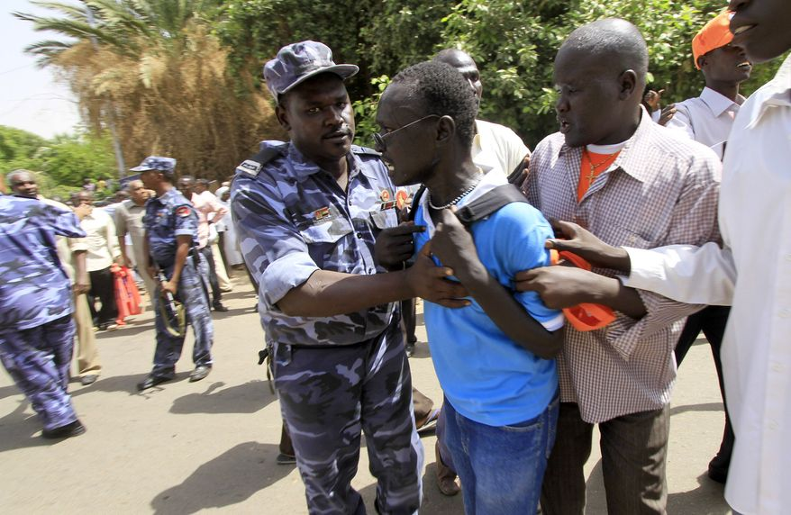 A southern Sudanese pro-secession demonstrator is held by security forces on Saturday at a rally in Khartoum, Sudan. (Associated Press)