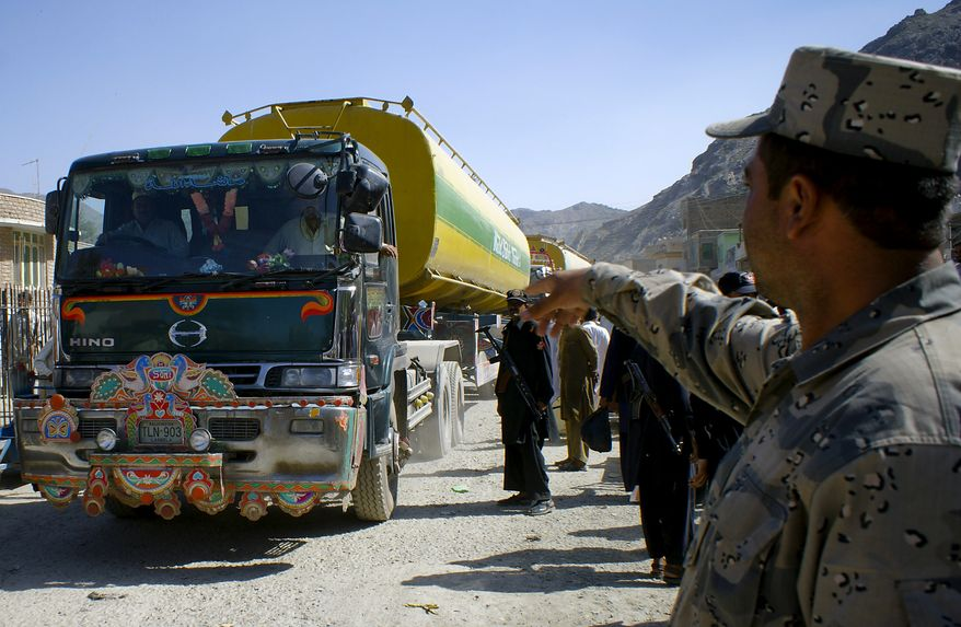 An Afghan police officer gestures for an oil tanker carrying fuel for NATO forces to enter Afghanistan through Pakistan's border crossing at Torkham on Sunday, Oct. 10, 2010. Pakistan reopened the key border crossing to NATO supply convoys on Sunday, ending an 11-day blockade imposed after a U.S. helicopter strike killed two Pakistani soldiers. (AP Photo/Qazi Rauf)