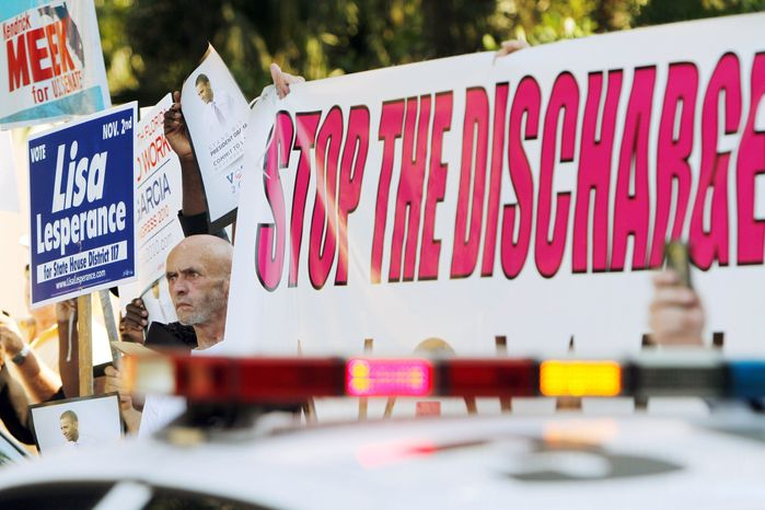 """ASSOCIATED PRESS Larry Whitt, who left the Navy after serving 12 years because he is gay, joins other protesters who watched President Obama arrive in Coral Gables, Fla., on Monday. Mr Whitt was there to protest the """"don't ask, don't tell"""" policy."""