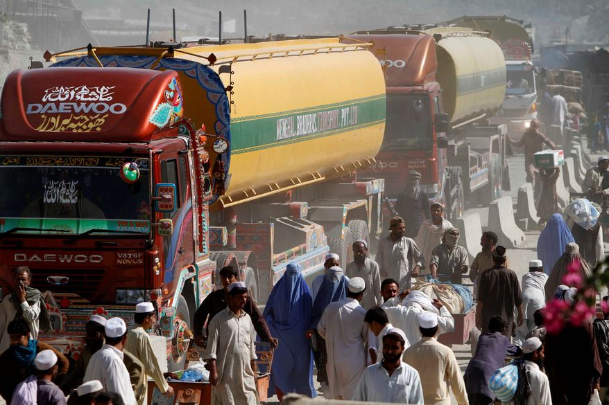 NATO fuel tankers enter Afghanistan through Pakistan's border crossing in Torkham, east of Kabul, Afghanistan, on Sunday. Pakistan reopened the key border crossing to NATO supply convoys, ending an 11-day blockade that was imposed after a U.S. helicopter strike mistakenly killed two Pakistani soldiers. (Associated Press)
