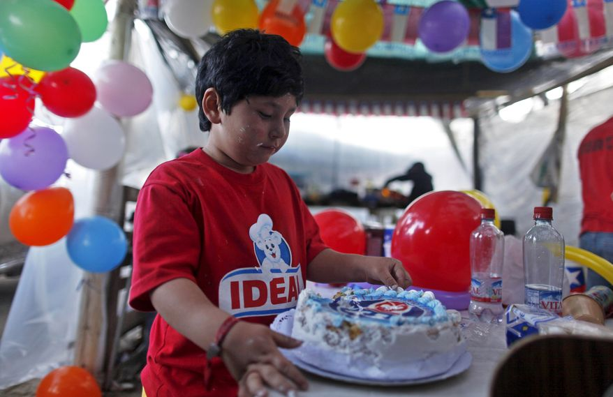 Arturo Zamora, son of trapped miner Victor Zamora, looks at a cake during the celebration of his father's 34th birthday at the San Jose mine near Copiapo, Chile, on Sunday, Oct. 10, 2010. After more than two months trapped deep in the gold and copper mine, 33 miners are close to being freed. (AP Photo/Natacha Pisarenko)
