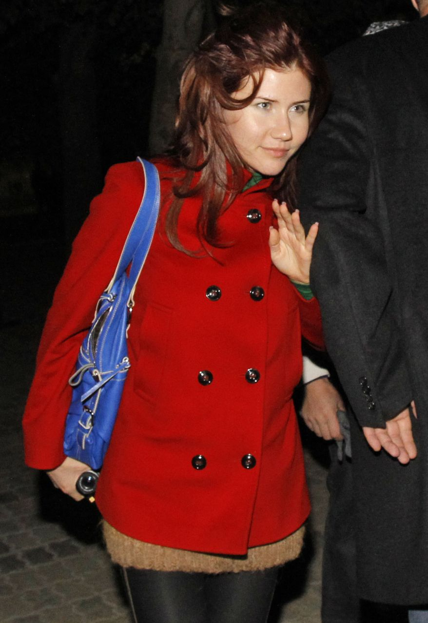 ** FILE ** Anna Chapman, a Russian national who was deported from the United States this summer for alleged spying for Russia, is seen with an unidentified security man at a ceremony for a U.S. astronaut and two Russian cosmonauts at the Russian-leased Baikonur cosmodrome in Kazakhstan on Thursday, Oct. 7, 2010. (AP Photo/Dmitry Lovetsky)