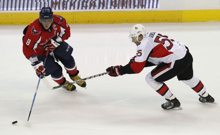 ASSOCIATED PRESS Washington Capitals' Alex Ovechkin (8), of Russia, keeps the puck away from Ottawa Senators' Sergei Gonchar (55), also of Russia, during the second period of an NHL hockey game in Washington on Monday, Oct. 11, 2010.