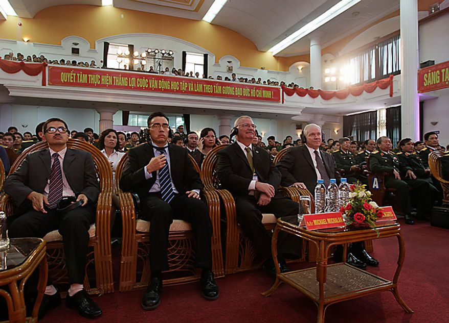 Defense Secretary Robert Gates, seated right, listens to the translation of his introduction before speaking at Vietnam National University in Hanoi, Vietnam, Monday, Oct. 11, 2010. Seated to Gate's left is Michael W. Michalak U.S. Ambassador to Vietnam. (AP Photo/Carolyn Kaster, Pool)