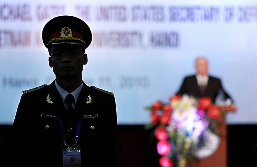 A member of Vietnam's military is seen in silhouette as he stands watch at left as Defense Secretary Robert Gates speaks at Vietnam National University in Hanoi, Vietnam, Monday, Oct. 11, 2010.  (AP Photo/Carolyn Kaster, Pool)