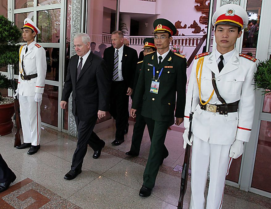 Defense Secretary Robert Gates, second from left, is escorted to his motorcade after meeting with Vietnam's Prime Minister Nguyen Tan Dung, not seen, at the Prime Minister's office in Hanoi, Vietnam, Monday, Oct. 11, 2010.  (AP Photo/Carolyn Kaster, Pool)