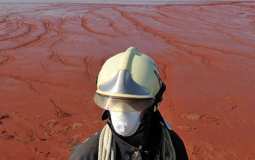 A Hungarian firefighter wearing protective mask and clothing stands guard at the red sludge reservoir, where a rupture caused deadly sludge flood in Kolontar, Hungary, Sunday, Oct. 10, 2010. The population of Kolontar was evacuated Saturday, and the neighboring town of Devecser with a population of 5,300 is also in the likely path of a new sludge deluge.  (AP Photo/Bela Szandelszky)