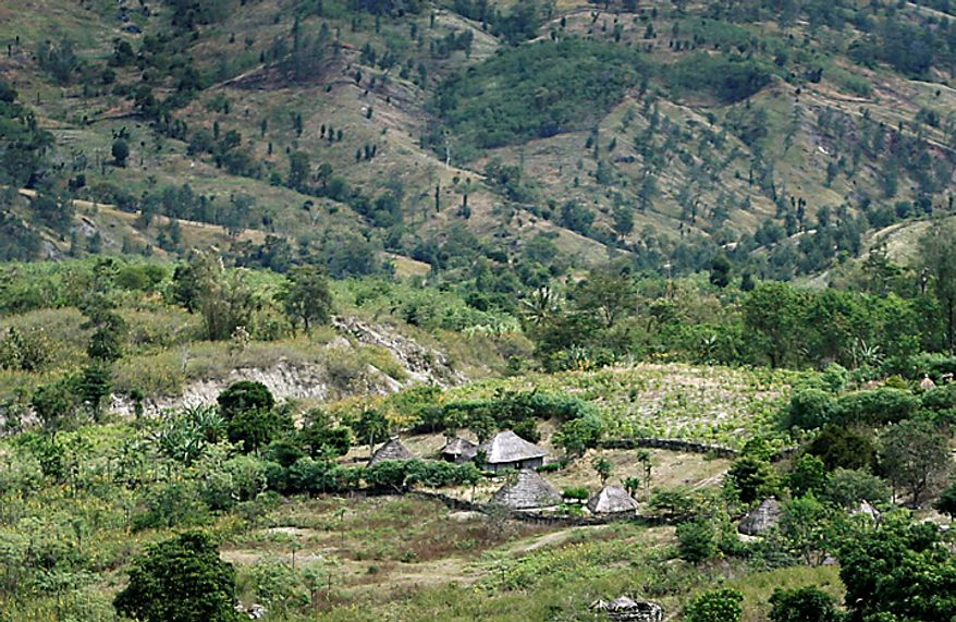 In this photo taken on Thursday, July 8, 2010, teepee-shaped huts, one of which belongs former leprosy patient Adelino Quelo, 68, sit against a wall of mountains in Malelat, West Oe-cusse, overlooking the East Nusa Tengara province of Indonesia. Adelino Quelo's fingers, toes and parts of his hands and feet are missing. Only stubby knobs remain, keeping him from standing, gripping and bathing himself. East Timor is one of just two places worldwide where leprosy is still widespread, and the country has now declared war on the age-old scourge. (AP Photo/Wong Maye-E)