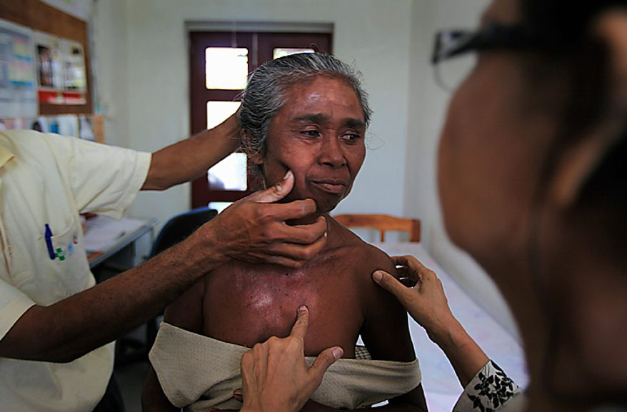 In this photo taken on Tuesday July 6, 2010, Dr. Rosmini Day, 62, a retired leprosy expert from Indonesia, right, examines leprosy patient Izabel Afdan, 52, center, at a health center, in Oe-sillo, 14 kilometers (9 miles) west of Oe-cusse town, East Timor. East Timor is one of just two places worldwide where leprosy is still widespread, and the country has now declared war on the age-old scourge. (AP Photo/Wong Maye-E)