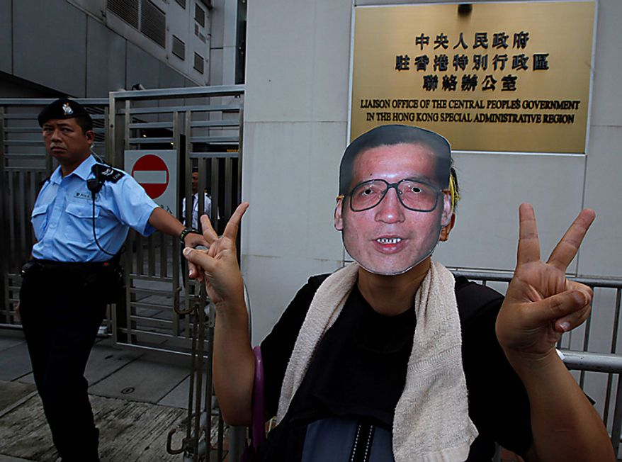 A pro-democracy protester gestures while wearing a mask of Chinese dissident Liu Xiaobo as he and others demand Liu's release outside China's Liaison Office in Hong Kong Monday, Oct. 11, 2010. The imprisoned Chinese dissident who won this year's Nobel Peace Prize was allowed to meet with his wife and told her in tears that he was dedicating the award to victims of a 1989 military crackdown on pro-democracy protesters, his wife and a close friend said.  (AP Photo/Kin Cheung)
