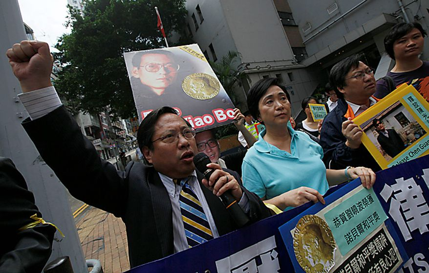 Pro-democracy protesters carry pictures of Chinese dissident Liu Xiaobo as they demand his release outside China's Liaison Office in Hong Kong Monday, Oct. 11, 2010. The imprisoned Chinese dissident who won this year's Nobel Peace Prize was allowed to meet with his wife and told her in tears that he was dedicating the award to victims of a 1989 military crackdown on pro-democracy protesters, his wife and a close friend said.  (AP Photo/Kin Cheung)