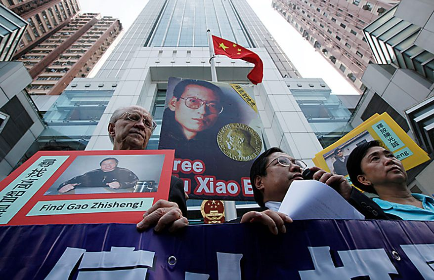 Pro-democracy protesters hold pictures of Chinese dissident Liu Xiaobo while demanding his release outside China's Liaison Office in Hong Kong Monday, Oct. 11, 2010. The imprisoned Chinese dissident who won this year's Nobel Peace Prize was allowed to meet with his wife and told her in tears that he was dedicating the award to victims of a 1989 military crackdown on pro-democracy protesters, his wife and a close friend said.  (AP Photo/Kin Cheung)
