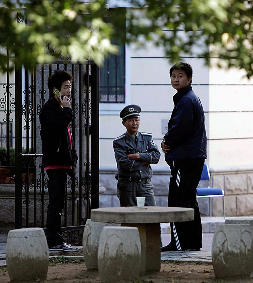 Plain clothes security personnel stand guard at a side entrance to a residential compound where Liu Xia, the wife of this year's Nobel Peace Prize winner Liu Xiaobo, is held under house arrest in Beijing on Monday, Oct. 11, 2010. Liu Xia confirmed in a Twitter message that she had been placed under house arrest since Friday. (AP Photo/Ng Han Guan)