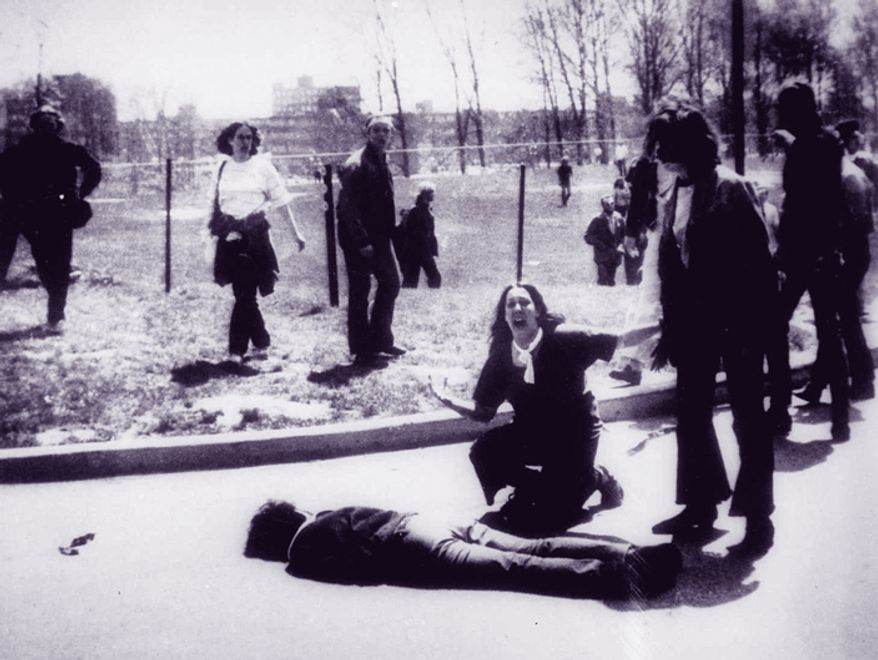 ** FILE ** Mary Ann Vecchio gestures and screams as she kneels by the body of a student lying face down on the campus of Kent State University in Kent, Ohio, on May 4, 1970. (AP Photo/John Filo)