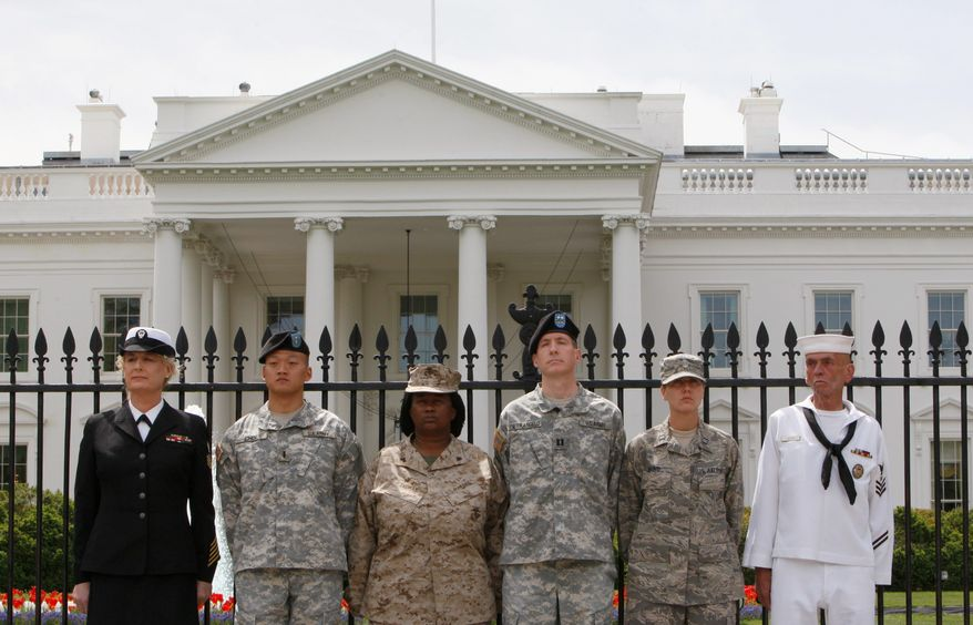 """From left, Petty Officer Autumn Sandeen, Lt. Dan Choi, Cpl. Evelyn Thomas, Capt. Jim Pietrangelo II, Cadet Mara Boyd and Petty Officer Larry Whitt stand together on April 16 after they handcuffed themselves to the fence outside the White House during a protest for gay rights. A federal judge issued a worldwide injunction Tuesday stopping enforcement of the """"don't ask, don't tell"""" policy, halting the military's 17-year-old ban on openly gay troops. (Associated Press)"""